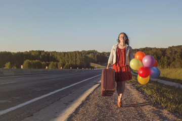 Happy young woman with balloons and large suitcase walking along road. Freedom, summer travel