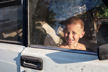 Little boy looking and squinting through window glass playing in old rusty car outdoor