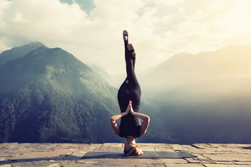 Photo sur Aluminium Ecole de Yoga Young woman doing complex Yoga exercise headstand with Namaste asana. Amazing Yoga landscape in beautiful mountains