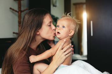 Portrait of happy mother kissing her baby together at home