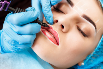 Cosmetologist making permanent makeup on woman's face Wall mural