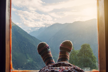 Legs in Warm socks of traveler near window with Himalaya high Mountains travel view. Freedom concept, relax and enjoy mountain view from indoor