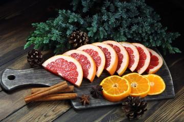 грейпфрут и мандарины с еловой веткой и шишками