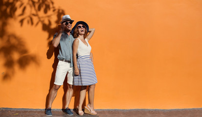 Happy smiling couple near orange sunny wall outdoor. Summer vacation, enjoy holiday