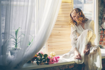 Beautiful young woman sitting on the window at home