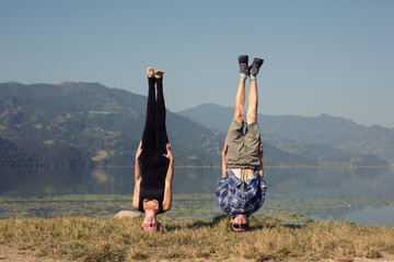 Couple of young yogis stand on his head while doing yoga headstand asana. Beautiful mountain lake landscape background. Complex amazing yoga picture
