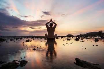 Yoga Silhouette man sitting on the beach at sunset. Reflection in the water, yoga, meditation, relaxation and harmony