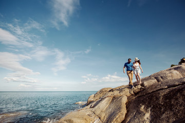 Young love couple of hipsters travelling in summer vacation. Man and woman walking on beautiful sea shore