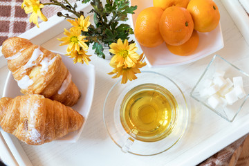 Cup of tea, croissant, chrysanthemum flowers and tangerines in tray on the table. Cozy home concept. Coloring and processing photo