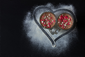 Delicious vanilla and chocolate pannacotta with sugar hearts in a glass on black table with painted heart.