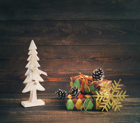 Christmas gifts. Festive boxes in colourful paper with a wooden decorative New Year tree on a wooden background. Holidays gift background