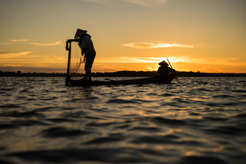 Silhouette of traditional fisherman throwing net fishing lake at