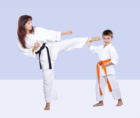 Mother and son are training kick in karategi