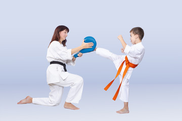 Son and mother are training kick in karategi