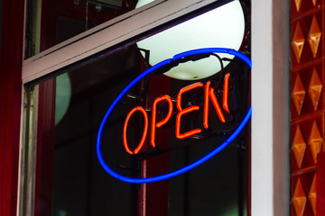 Neon sign of a store with the word Open and indoor lamp globe