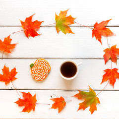 Cup of coffee and pumpkin cookie on white wooden background with
