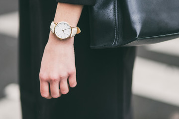 close up fashion details, young business woman holding her black elegant bag. wearing golden and white watch. ideal fall outfit accessories.