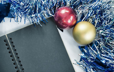 Toned Christmas background photo. Blank page of black notebook. Blue ribbon wreath.