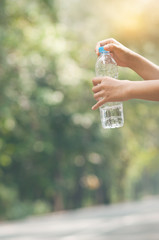 Close up Asian woman hand holding bottle of water on nature back