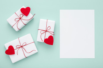 Valentine day composition: white gift boxes and red bows and red felt hearts with white card for text, photo template, pastel blue background. Top View. View from above.