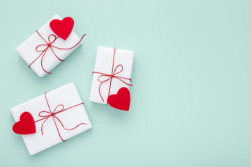 Valentine day background with white gift boxes with label and hearts on pastel blue background.