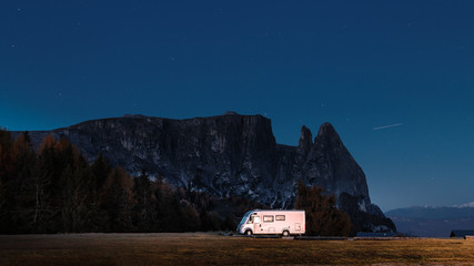 Camper van at rock and night star sky backround. Dolomiti mountains, Italy. Night scene with camper van.