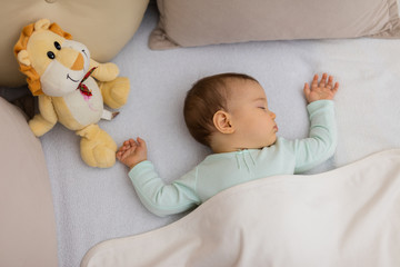 Adorable baby sleeping at night. Little girl in pajama taking a nap in dark room with toy / Baby Sleeping on the bed