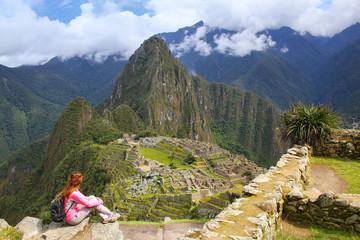 Woman enjoying the view of Machu Picchu citadel in Peru