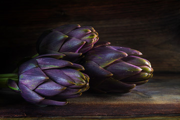 purple artichokes from italy on a dark rustic wooden board