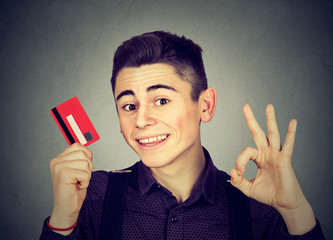 happy young man with credit card showing Ok sign