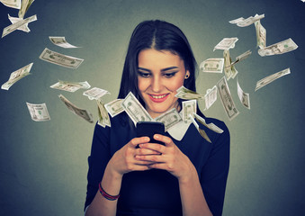 woman using smartphone with dollar bills flying away from screen.