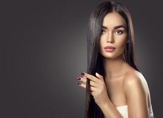 Beauty brunette model girl touching long healthy hair