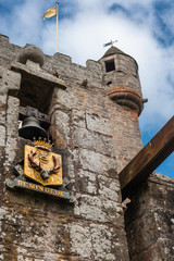 Cowdor, Scotland - June 2, 2012: The brown-gray stone structure of main gate of undamaged Cowdor Castle. Flag on top. Golden emblem wihth slogan. Guard tower.