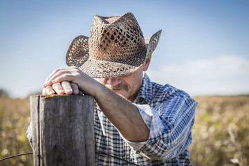 horizontal close up image of a caucasian cowboy praying by a fence post on a warm fall day.