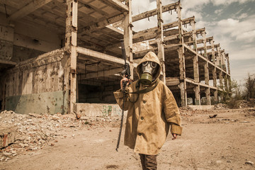 young boy stands with a gun in his hand. boy in a gas mask. boy in a protective cloak and hood. child standing near the destroyed building. a child soldier. young boy soldiers. laser tag game.