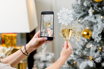 Photographing with smart phone a glass of sparkling wine with snow flake on the Christmas tree background