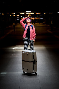 Mature Asian woman with suitcase looking upward to source of con
