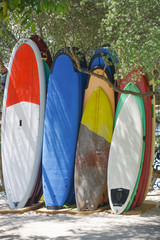 Set of different color surfboards in a stack by ocean