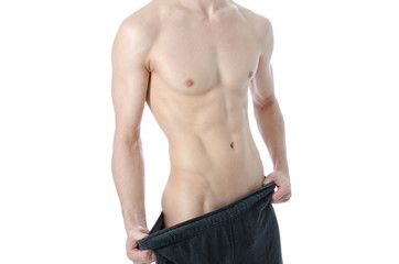 Lose weight. Young guy with a beautiful figure after the diet.