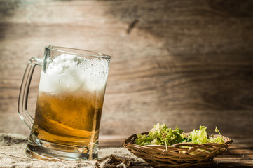 Frothy beer poured from cup on empty wooden background