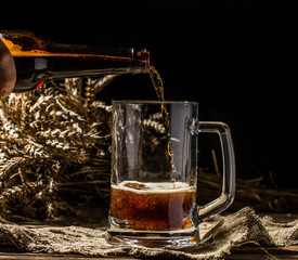 Foamy beer poured into mug standing on empty wooden background