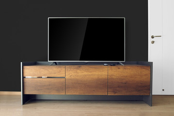 Led TV on TV stand in empty room with black wall. decorate in loft style.