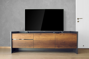 Led TV on TV stand in empty room with cement wall. decorate in loft style.