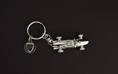 Silver-chrome keychain with an  old super fast model on leather background