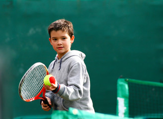 Little tennis player on a blurred green background