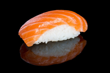 Sushi nigiri with salmon on black background with reflection. Ja