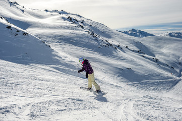 Snowboarder riding at French Alps mountain slopes