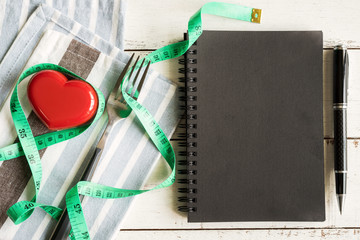 Red heart and notebook with measure tape