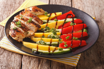 salad of grilled chicken with fresh mango, avocado, sweet pepper with balsamic sauce close-up. horizontal