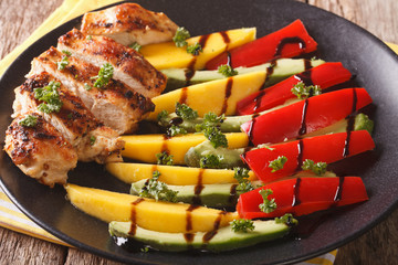 Grilled chicken breast with mango, avocado and pepper close-up. Horizontal